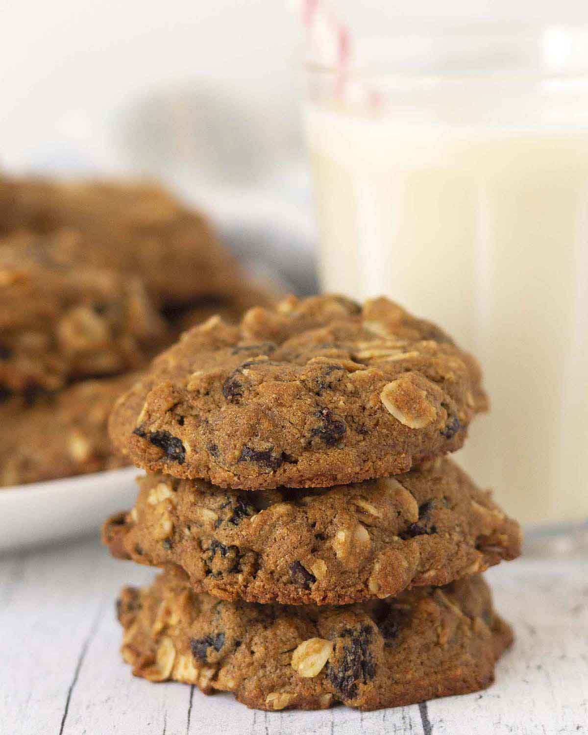 Image shows three oatmeal cookies with raisins stacked on top of each other.