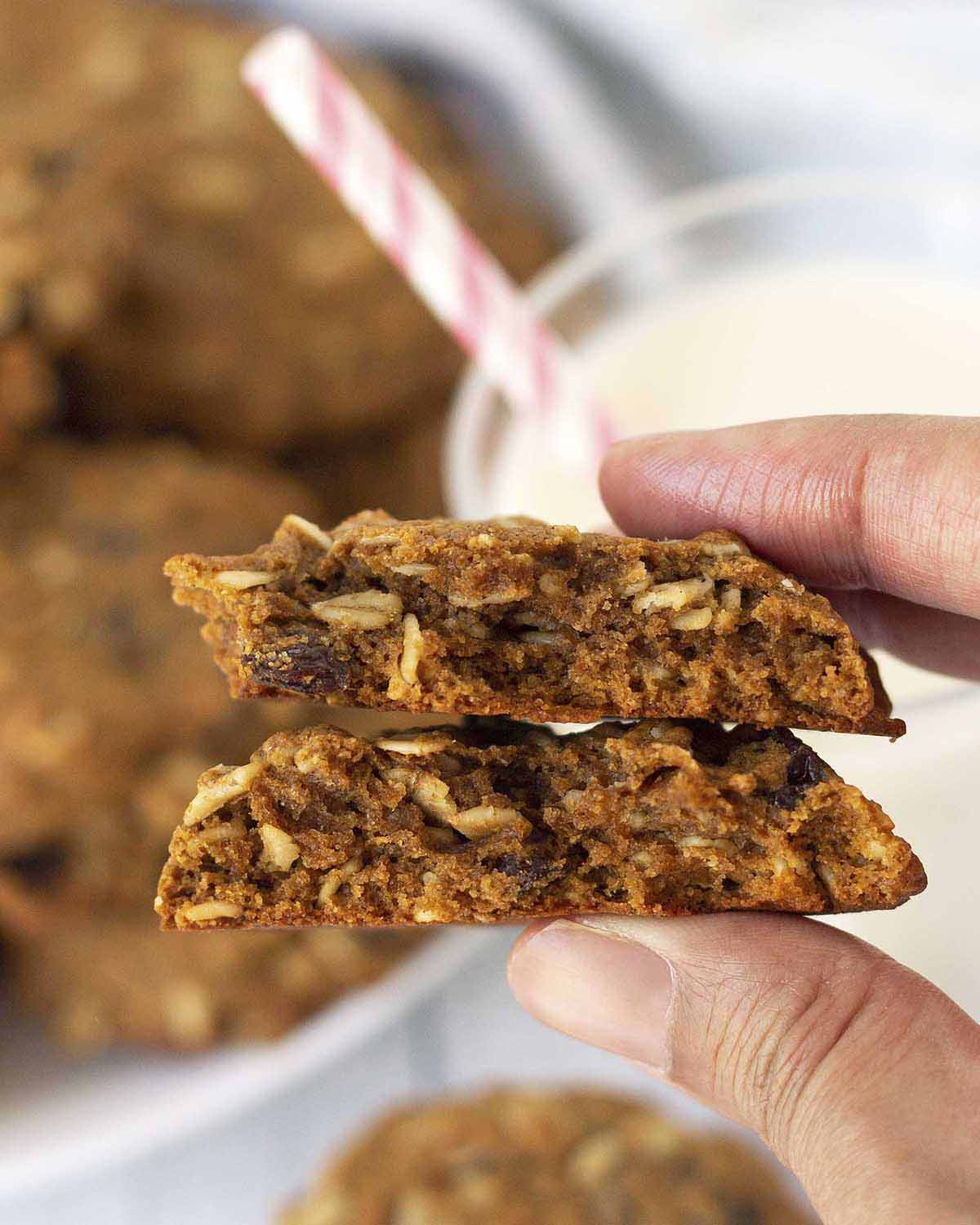 Image shows a hand holding an oatmeal raisin cookie that has been broken in half to show the soft inside of the cookie.