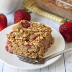Image shows an egg-free baked strawberry oatmeal slice on a white plate, a fork is also on the plate.