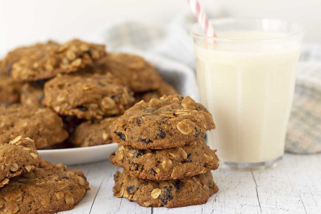 A stack of three oatmeal raisin cookies, more cookies are on a plate behind the stack, a glass of milk sits to the right.