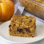 Image shows an egg-free baked pumpkin oatmeal slice on a white plate, a fork sits behind the plate.