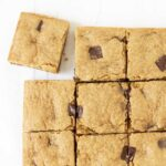 An overhead shot of a batch of gluten-free blondie brownies, the one in the top left corner is pulled away from the rest.