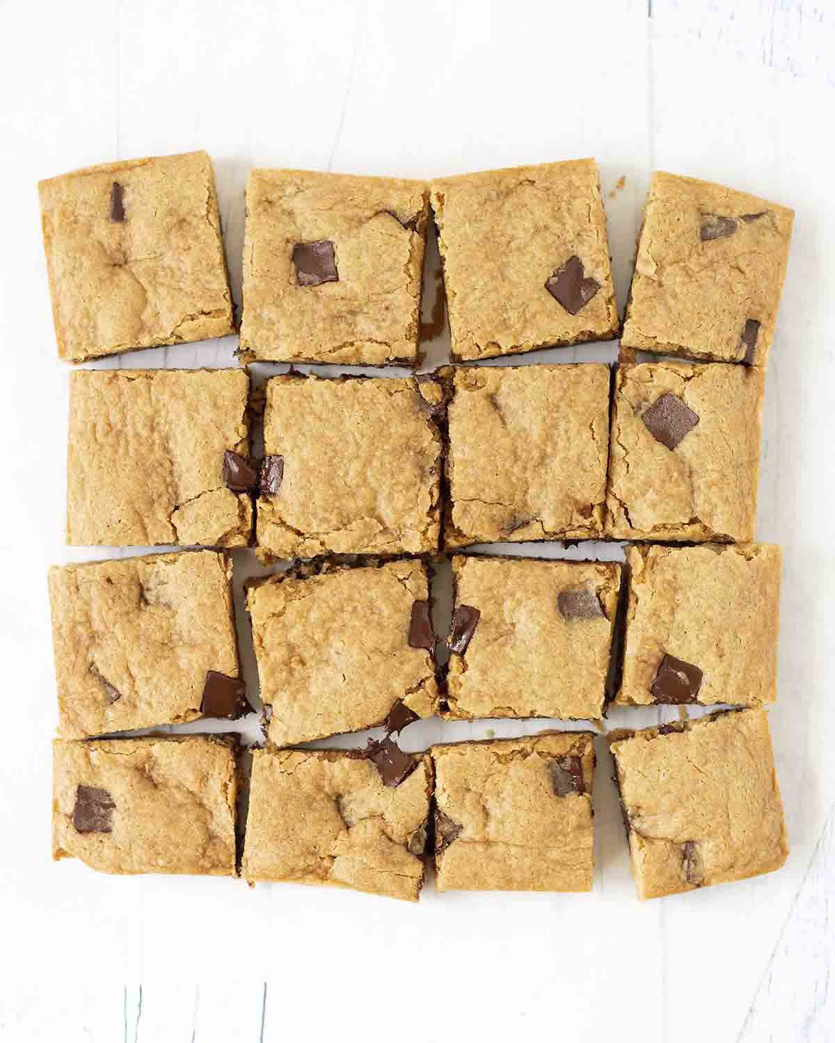 An overhead shot showing a batch of freshly baked and sliced vegan blondies on a table.