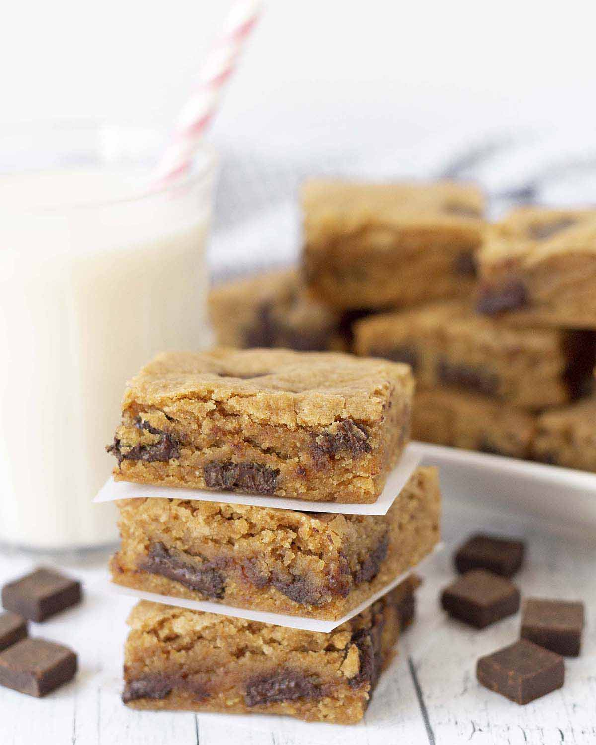 Three vegan gluten-free blondies stacked on top of each other, a glass of milk and more blondies sit behind the stack.