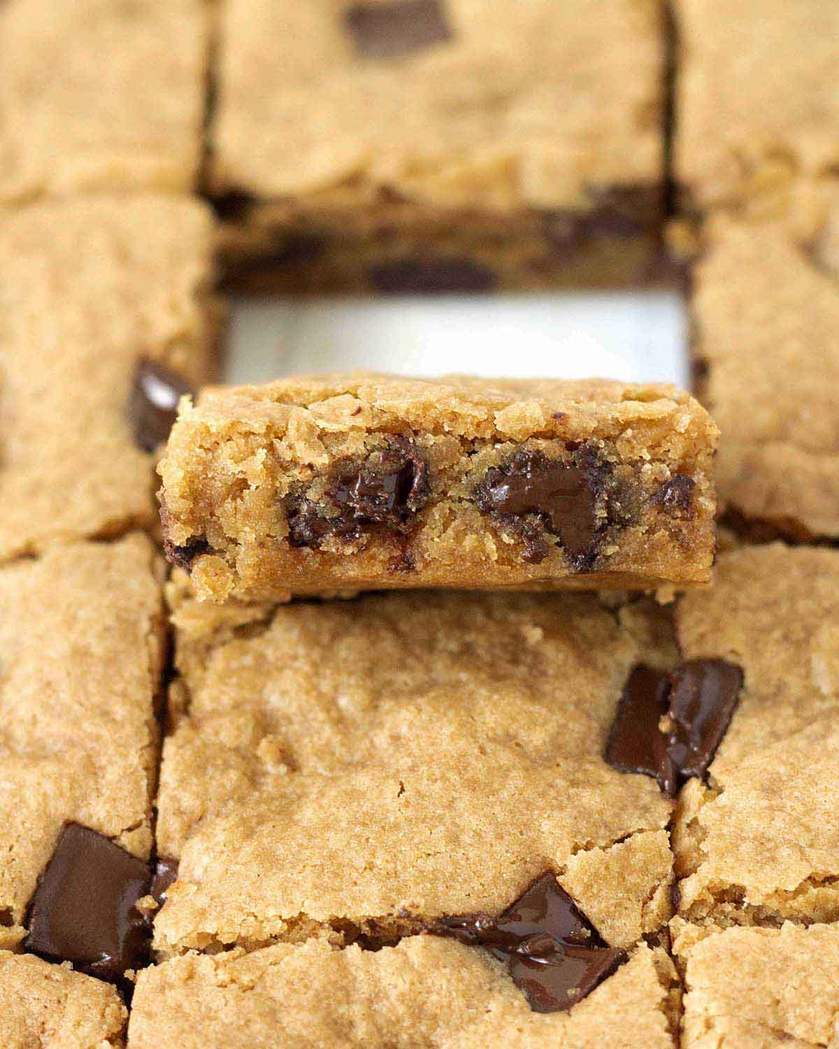 Image shows vegan gluten-free blondies, one blondie is tilted up to show the chewy inside and melty chocolate chunks inside.