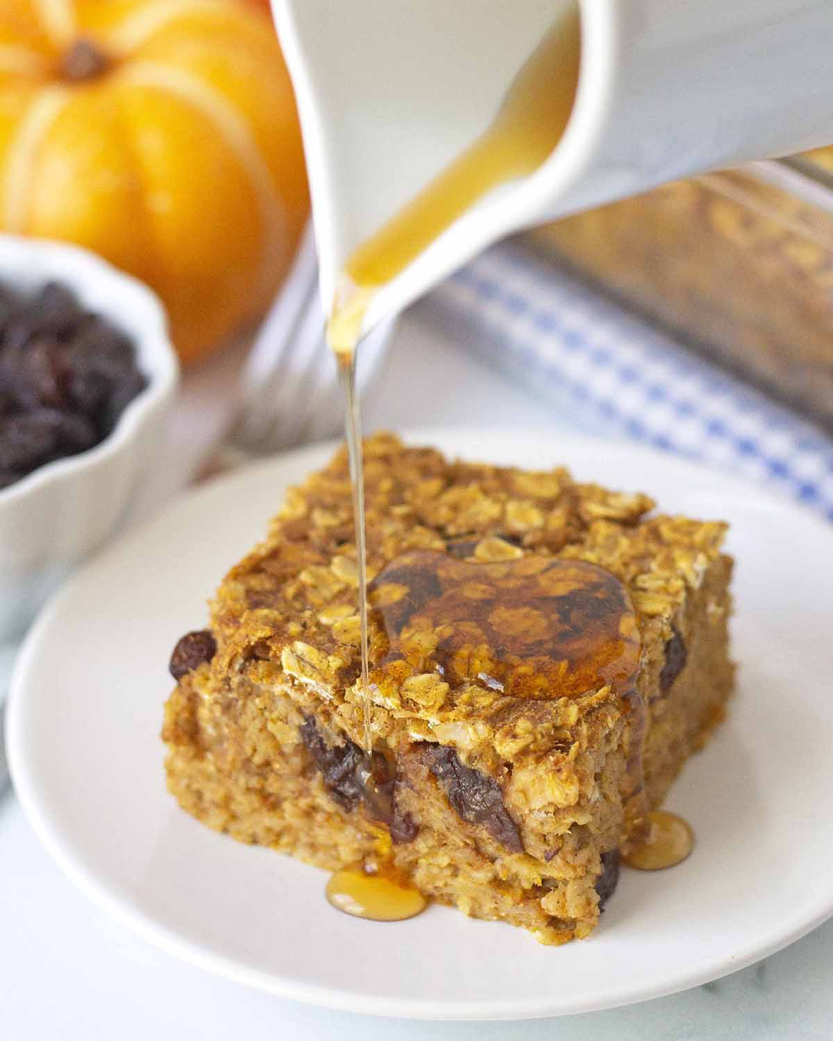 Maple syrup being poured onto a slice of vegan pumpkin spice baked oatmeal.