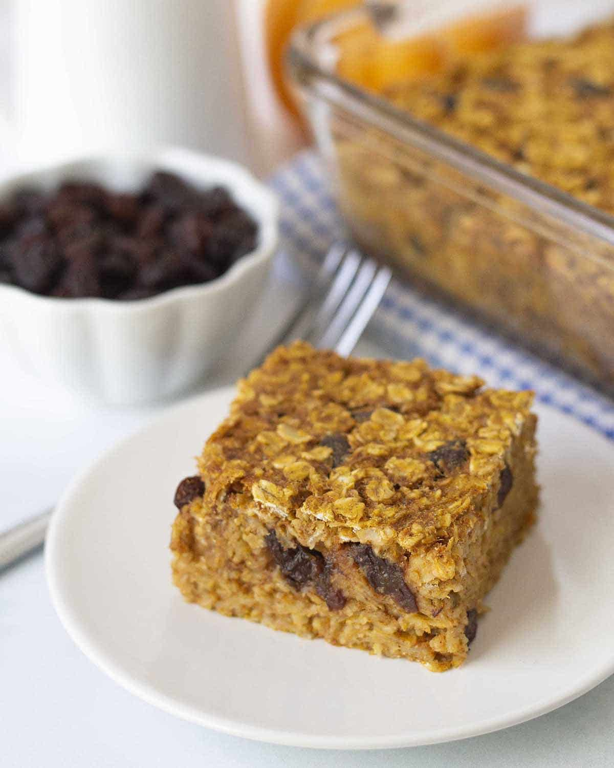 A close up shot of a slice of dairy-free baked oatmeal on a plate, a fork and a small bowl of raisins sits behind the plate.