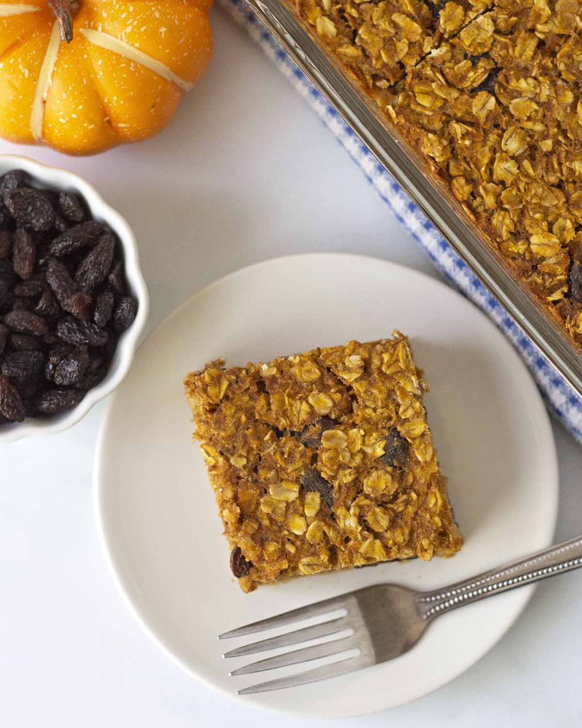 An overhead shot showing a slice of baked oatmeal with pumpkin on a plate, a fork also sits on the plate.