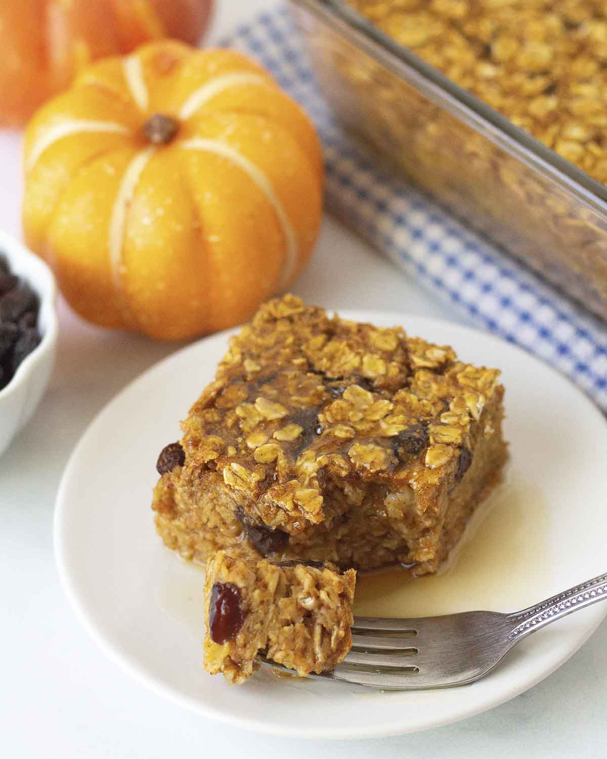 A square of pumpkin pie baked oatmeal on a white plate, a piece of the oatmeal is on a fork, the fork in on the plate.